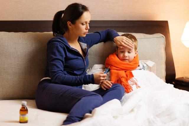 Mom taking temperature sick kid